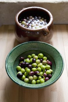 A bowl of raw olives(foreground) and a bowl of olives being cured in brine (background) - Roger Stowell / Getty Images