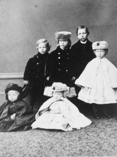 Left to right: Prince Henry of Prussia (1862-1929), Princess Charlotte of Prussia (1860-1919), Prince Wilhelm of Prussia (1859-1941), and their cousin Princess Victoria of Hesse and by Rhine (1863-1950). Princess Charlotte and Princess Victoria are both wearing hats. Seated in front of them are two younger children. Princess Elisabeth of Hesse and by Rhine (1864-1918) is sitting on the right next to another child who is possibly Prince Sigismund of Prussia (1864-66).
