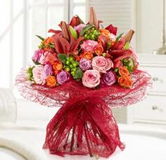 Sweet and Blooming... The Sweet and blooming Bouquet is just a darling gift. It is a wonderfully mixture of pink, red, orange, purple and green flowers. Beautifully arrange together in a hand tied design, this bouquet extends soft and feminine admiration.