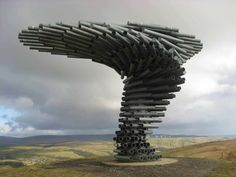 The Singing Ringing Tree, in Lancashire, UK. The tree is constructed of stacked pipes of varying lengths, orientated to lean into the directions of the prevailing wind. As the wind passes through the different lengths of pipe, it plays different chords. Each time you sit under the tree, looking out through the wind, you will hear a different song.