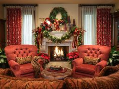 """Ralph Lauren chairs upholstered in crimson chenille and a tuffed leather ottoman create comfortable seating in front of the family room fireplace. Wide garland and holiday decor enhance the massive hand-carved limestone mantel. - """"Decorating for Christmas, Old World Style"""""""
