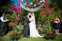 Pretty tissue paper flowers add a bit of whimsy to this chuppah.Related: 130  Spectacular Wedding Decoration Ideas