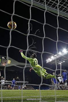 Chelsea's Belgian goalkeeper Thibaut Courtois (C) cannot stop the header from Tottenham Hotspur's English midfielder Dele Alli (2nd R) as Tottenham take the lead during the English Premier League football match between Tottenham Hotspur