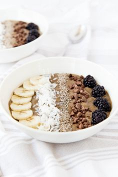 Breakfast bowl with banana, shaved coconut, chocolate, and berries.