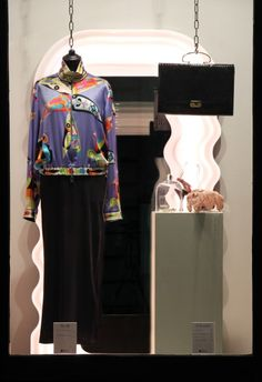 On the left wearing: Emilio Pucci colorful silk bomber jacket, Dolce&Gabbana black dress.  On the pedestal:  1980s croc print leather purse, 1950s headbend with silk flowers and tulle, 1970s platform sandals, 1960s Florenza jewelry set.
