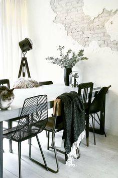 Eetkamer met veel zwart. Over de stoel hangt de zwarte lamswollen plaid van het Zweedse merk Klippan. Een heerlijke warme plaid in de stoere kleur zwart. De ene kant is donkerder dan de andere kant door de manier van weven. Deze heerlijke zwarte plaid staat geweldig op je bank. En hij is nog behaaglijk warm ook. Deze wollen plaid is verkrijgbaar bij webshop Ookinhetpaars.