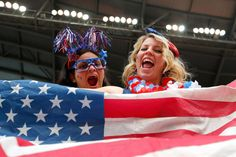 Fans at the United States versus Australia match hold up an American flag and don red, white and blue as they cheer on the U.S. team during the 2015 FIFA Women's World Cup game on June 8, 2015. The United States secured their first victory against Australia with a final score of 3-1.