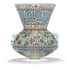 A GILT AND ENAMELLED CLEAR GLASS MOSQUE LAMP  PROBABLY BROCARD, CIRCA 1880  Of squat body with flaring neck, with six applied glass loops, the delicate floral decoration with radiating floral sprays and lotus blossoms, the lower register with medallions of pseudo calligraphy, the upper register with a very elegant inscription in thuluth reserved on blue ground, the foot missing  10¾in. (27.4cm.) high