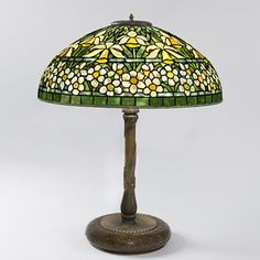 "A Tiffany Studios New York ""Jonquil-Daffodil"" leaded glass and bronze table lamp, featuring orange/yellow jonquils in the upper portion and white petaled flowers with orange/yellow centers, all resting on a green leafed ground."