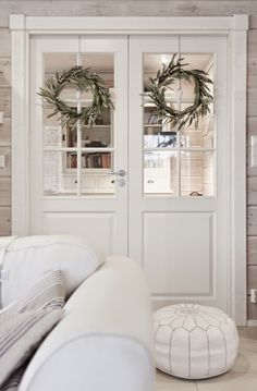 pariovet, hirsitalo, double doors, pair doors, white home, ovikranssi, kranssit, white ottoman, white pouf, moroccan pouf, moroccan ottoman White Ottoman, Log Home Living, Country Interior, White Rooms, Scandinavian Home, White Houses, Dream Decor, Cushions On Sofa, Home Staging