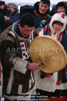 A Chukchi man playing a shamans drum. Northern Siberia, Russia