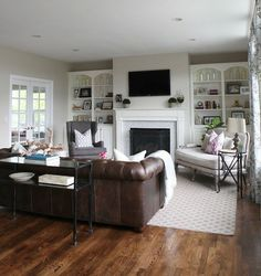 ideas to decorate a living room to achieve balance and symmetry with a furniture layout using a couch, chairs, area rug and coffee table