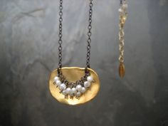 This necklace has a black oxidized sterling silver chain, and a 14k gold plated sterling silver plaque in the center. The plaque has an irregular shape