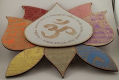 """$45 - Lotus - Buddha - Om wall hanging:  This unique wall hanging is made up of multiple pieces of painted wood. Each petal has an engraved image of a Tibetan prayer flag, and the main petal has the OM symbol surrounded by a saying from the Buddha. """"Better than a thousand hollow words is one word that brings peace"""". Approx dimensions are 10""""high x14"""" wide. Standard toothed hanger on the back."""