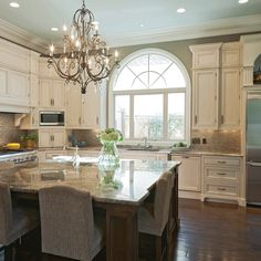Neutral colors, vintage white cabinets, backsplash, and the chandelier!