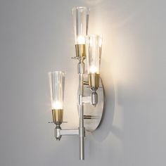 Champagne Flute Tiered Wall Sconce- 3 Light Sparkling champagne flute glass reflects brilliant halogen light beautifully on your wall from this glistening wall sconce. Pivoting steel arms in brushed nickel finish are accented with natural brass to warm up the mix