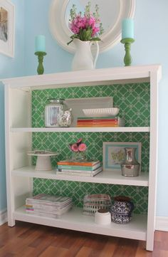 I love this! Giving plain book cases a make over by wallpapering the back panels. #loveit #diy #homedecor