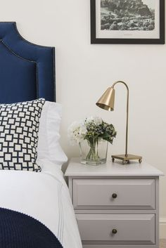 Sophisticated bedroom features a blue velvet headboard with silver nailhead trim on bed dressed in white and blue stitched hotel bedding and a navy cat& cradle pillow next to a gray nightstand adorned with brass knobs topped with a brass task lamp. Blue Headboard, Velvet Headboard, Blue Bedding, Dark Blue Bedroom Walls, Gold Bedroom, Bedroom Decor, Blue Walls, Bedroom Inspo, Bedroom Ideas