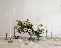 Cool toned tablescape with silver compote, silver and white gold candlesticks and an array of glass and silver mercury votives