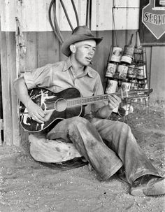 """June 1940. Pie Town, New Mexico. """"Farm boy playing guitar in front of the filling station and garage."""""""