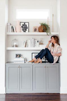 brighton keller sitting on living room bookshelves, Sherwin Williams Chelsea Grey Paint color on cabinets