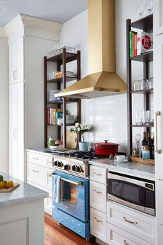 Love the contrasting dark wood bookshelves to either side of the cooktop against the classic white cabinets.