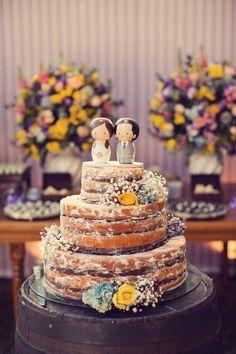 Bolo naked cake com recheio de chocolate e rosas para decorar. Como topinho de bolo, uma representação fofa do casal em madeira.