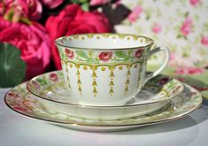 Adderleys Sicily vintage English bone china teacup, saucer and tea plate trio. Beautiful hand painted pink roses and green foliage border with an inner green and yellow 'tassel' style pattern and gold gilded rims. The teacup has an inner border on the rim. 9cm wide at the rim x 5.5cm tall approx. Saucer 14cm wide and Tea Plate 17.5cm wide.   Sicily pattern made by Adderleys Ltd., Daisy Bank Pottery, Longton, Staffordshire. c.1926+. In excellent condition.