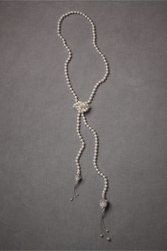 """""""Coco's Vision Lariat"""" byDebra Moreland forBHLDN (bhldn.com/shop).Inspired by iconic French fashionistas, Paris by a string of pearls tipped with sparkling tassels can be worn as a necklace or looped twice around your waist. 57""""L; large pendant: 4""""L, 0.75""""W; small pendant: 2.75""""L, 0.5""""W. Glass pearls, rhodium plated brass, Swarovski crystals. Handmade in USA.Price: $425"""