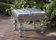 IMAX Damron Aluminum Ottoman - The Damron aluminum ottoman has a unique tufted upholstery look cast in aluminum and adds a touch of whimsy when used as a petite side table.