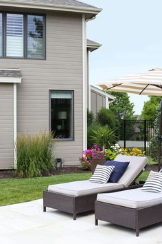 A gorgeous backyard showing that the addition of color can completely change the space. Love the chaise lounges, navy blue striped pillows, striped umbrellas, bright pink roses, and annuals in planters. #EasyElegance #ad #RosesYouCanGrow