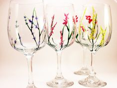 These wine glasses are sold as a set of four and are made to order. This is one of my most popular sets - a really wistful and lovely design that has a different type of wild flower on each glass. Do you know what inspired this set? Those pretty flowers on the side of the road or on highway medians! I painted flowers in bright pink, red, golden rod yellow, and a pale periwinkle blue. * If you like this idea but would like a certain type of wild flower or different type of wine glasses, Id be…