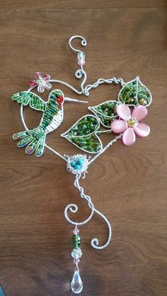 Wire wrapped beaded sun catcher with flowers and hummingbird and nest.