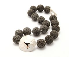 cracked domed and lava necklace with a hidden garnet in the middle. This one was sold through www.baxtersgallery.co.uk
