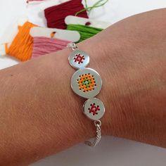 Geborduurde armband met rood oranje en details in roze en groen. #geborduurd #armband #corinarietveld #sieraden #sieradenwebshop #jewelry #jewelrydesigner #embroidery #bracelet