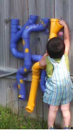 children building with golf balls pvc and nutsBall run made of pvc pipe, painted yellow and purple, twists and turns. Golf balls supplied in a metal bucket near by.On side of playhouses Backyard Playground, Backyard For Kids, Diy For Kids, Preschool Playground, Outdoor Toys, Outdoor Fun, Toddler Playhouse, Kids Play Area, Play Areas