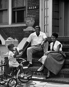 Baseball star Jackie Robinson with his wife Rachel as young son Jackie Jr. drinks a glass of milk, on the front steps of their home, Brooklyn, New York, July 1949 Photograph by Nina Leen. Jackie Robinson, Robinson Family, My Black Is Beautiful, Black Love, Black Men, Fosse Commune, 1940s, Vintage Black Glamour, Vintage Beauty