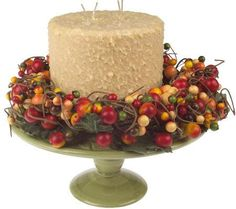 Extra large, round birthday-looking cake, working candle, on a green ceramic pedestal. The cake-candle ringed with a fall colors berry like round garland. Valerie Parr Hill retired.