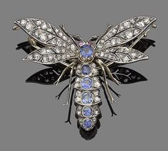A sapphire, ruby and diamond dragonfly brooch, circa 1890.  The abdomen centrally-set with cushion-shaped sapphires, between duos of rose-cut diamonds, to similarly-cut diamond wings, the head highlighted with two circular cabochon ruby eyes, mounted in silver and gold, detachable brooch fitting, length 5.4cm