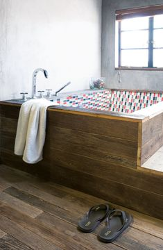 Modern Lilong House Renovation in Shanghai - Photo 10 of 11 - All of the floorboards in the house, as well as the wooden panels encasing the bathtub in the main bathroom, are made of antique door frames.