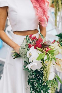 Pink hair bride in two piece wedding dress with cascading tropical wedding bouquet