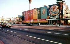 """Aquarius Theatre, photo taken in 1970 on Sunset Blvd. in Los Angeles, CA, two full years after it was painted  in bold colors for the opening of the musical """"HAIR."""" 6230 Sunset Boulevard. The historic structure was painted for the opening of Hair in 1968. Eric Clapton, Janis Joplin, and Sal Mineo caught performances of the play during its two-and-a-half year run from 1969-1971."""