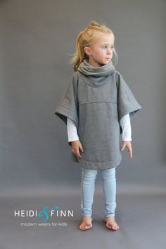 The Veritas cape is a simple, comfy and modern staple in any child's closet. This generous sized poncho style cape is a great 3 season piece. Made with stable knits that focus on volume vs drape, this cape is incredibly easy to sew. The practical hi-low hem and optional slim cowl or hood with various ears/embellishments make this a very versatile design that you will want to sew over and over again with many different results Perfect for Dress up too! The possibilities are endless! Thi...