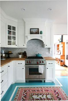 Love that range hood, the way the cabinets are finished to the ceiling, the butcher block counter tops, the corner cabinets.