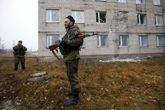 Pro-Russian separatists stand guard outside the building of a perinatal center damaged by what locals say was shelling by Ukrainian forces in the town of Pervomaisk, west of Luhansk, eastern Ukraine, November 15, 2014.