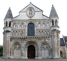 ROMANESQUE - ARCHITECTURE: Notre-Dame-la-Grande - Early 12th century - West facade - Elaborate bordered arcades house large seated or standing figures. Below that, wide band of relief stretches across the facade. Doorway deeply recessed and framed by series of arches resting on stumpy columns. Taller bundles of columns enhance turrets - their conical helmets nearly match the height of gable in center which rises above the actual height of roof behind it. LOCATION: POITIERS, FRANCE
