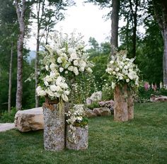 Backyard wedding altar - pretty floral arrangements on cut logs. Photo: A Bryan Photo / Event Planning & Design: Mariee Ami / Event Design, Floral Design: Wildflower Designs