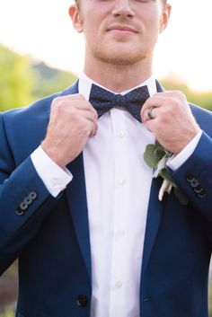 Navy blue grooms attire. Bow tie and navy blue suits are sure to make your groom look dapper!