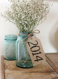 Rustic Burlap Table Tag. Put a bundle of flowers in the mason jar vase, tie rustic burlap tag around the neck of it to create the barn graduation party decor with a fresh flavor. http://hative.com/diy-graduation-party-decoration-ideas/