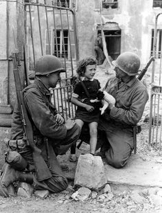 American soldiers comfort a little girl and her puppy after the invasion of Normandy , France, 1944